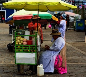 Una cholita e il suo carretto di succo d'arancia fresco