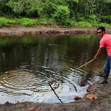 Comunero di San Pedro che mostra alla delegazione la presenza di petrolio nel km 20 del canale dell'ONP. Foto di Rebecca Pagani.