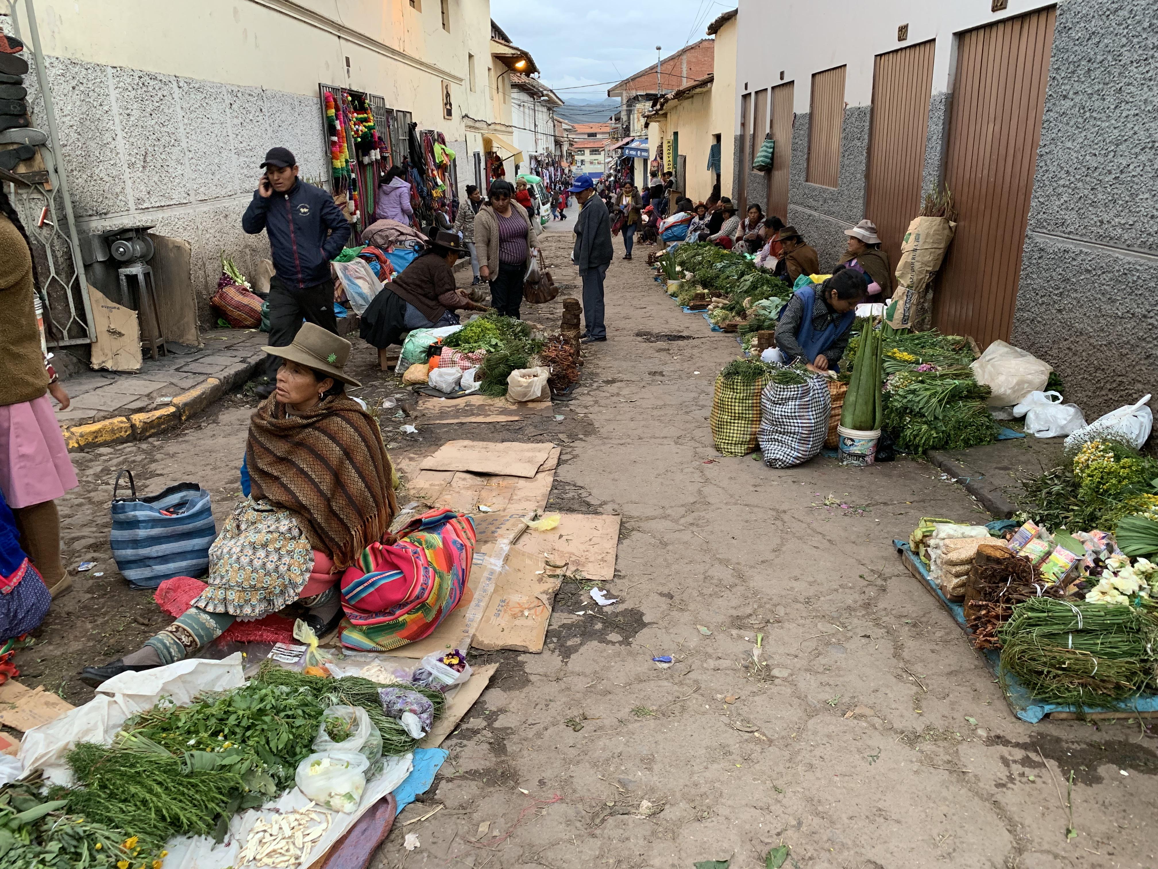 Persone mentre vendono i loro prodotti nelle stradine accanto al Mercado de San Pedro, Cusco